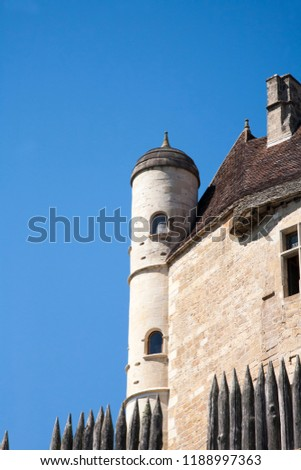round tower detail of Beynac Castle in the Dordogne, France with some sharpened wooden defensive stakes below and a deep blue sky above