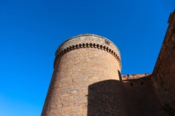 round tower of the medieval spanish castle la Calahorra against the blue sky