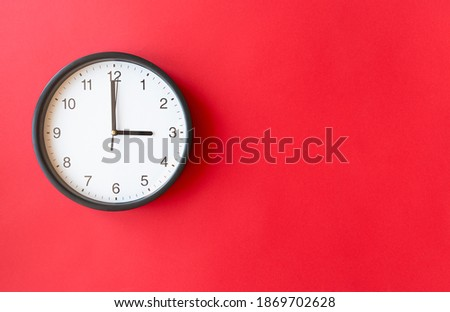 Round wall clock on red surface showing 3 o'clock, layout, top view, place for text Stockfoto ©