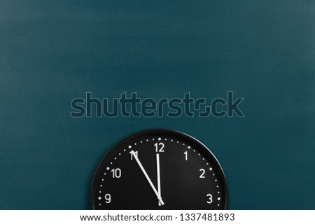 Round wall clock showing 5 minutes to midnight on chalkboard background. Crop image with space for promo copy #1337481893
