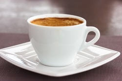 Round white ceramic cup with cappuccino latte coffee brown foam on square saucer on a table. A hot flavored aromatic drink in a cafe, restaurant in the morning, lunch at autumn season. Beverage theme.