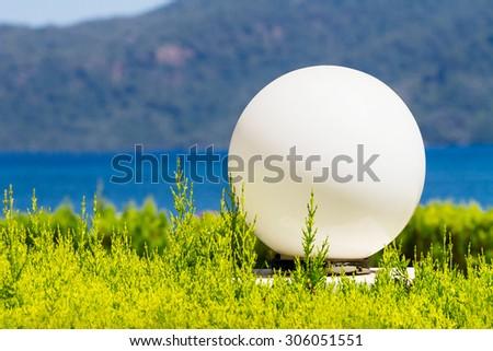 Round white lanterns in flower bed. Landscape background #306051551