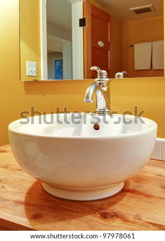 Round white sink with faucet and natural pine wood.