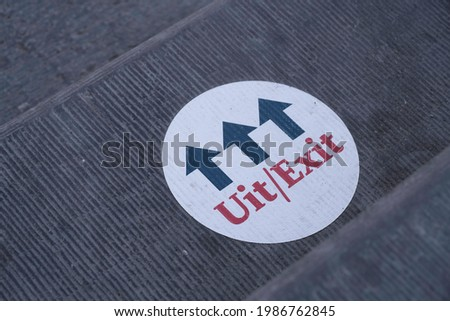 Round white sticker with arrows and the dutch text 'Uit' (Exit) stuck on a sidewalk in front of a store Stockfoto ©