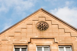 Round window, decorative detail of the facade on the pediment of an old historic building, Roth, Germany.