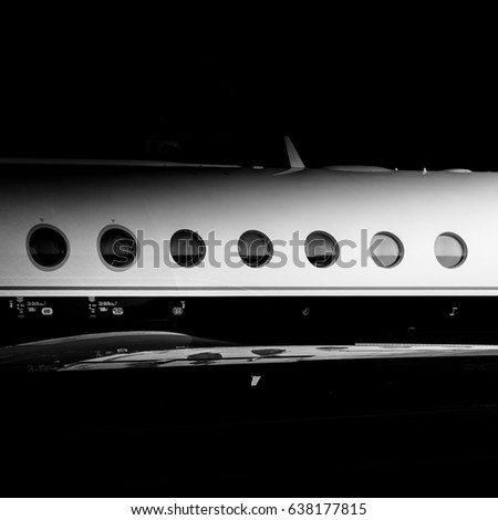 Round Windows of a private jet. Bizjet black and white. Only a few people can afford to travel on luxury...wealthy, vips, entrepreneurs and some lucky ones that make a pass from a friend.