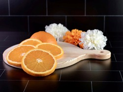Round wooden cutting board with a handle with a fresh orange sliced up and arranged on it with 3 artificial white and orange flowers sitting behind it on a black subway tile counter.  Fresh fruit.