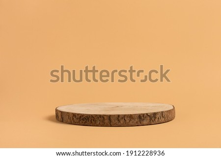Round wooden saw cut cylinder shape for product presentation on a beige background. Round geometric shape of the cylinder. eco style and minimalism