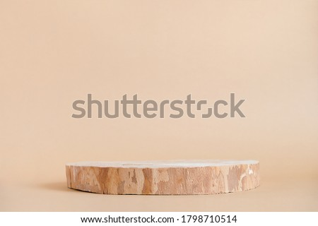 Photo of  Round wooden saw cut cylinder shape on beige background abstract background. Minimal box and geometric podium. Scene with geometrical forms. Empty showcase for eco cosmetic product presentation