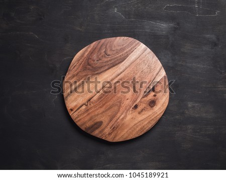 Round wooden tray or cutting board on black table. Top view of empty kitchen trendy rustic wooden tray saw cut imitation on black wooden background. Copy space for text. Food and menu background.