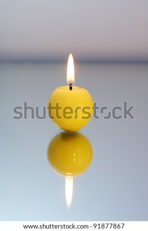 Round yellow candle burning on a reflective surface.