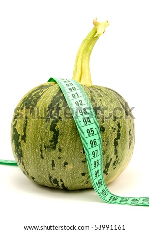 Round zucchini with measuring tape on white background