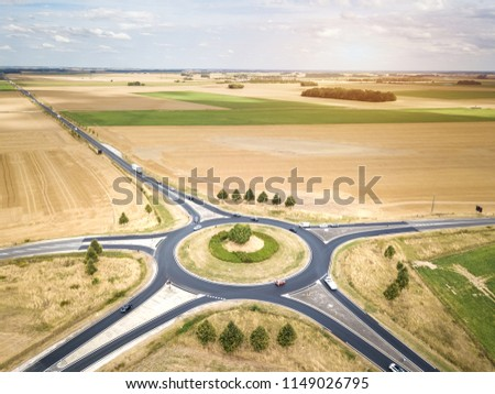 Roundabout drone aerial view with vehicles circling around the traffic circle lane, France country side rural road transportation, summer day, cars and trucks #1149026795