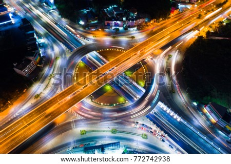 Roundabout intersection city road at night with vehicle light movement aerial view