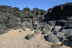 Rounded, black stones lay below volumes of petrified lava on the golden Skardsvík sand beach, Iceland