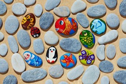 Rounded colorful stones pebbles shingle with pictures painted on them