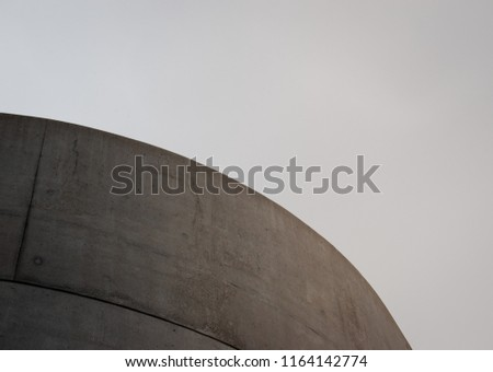 Rounded concrete structure in front of overcast sky. #1164142774