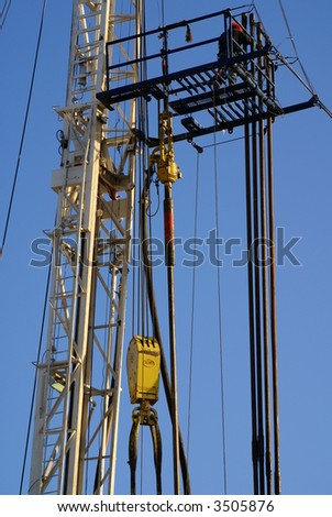 Roustabout works on high platform of oil drilling rig, Kern County, California - stock photo