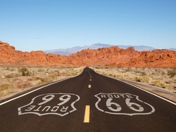 Route 66 pavement sign with Mojave desert red rock mountains.