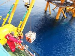 ROV crew deploys inspection class ROV into the sea next to wellhead platform.