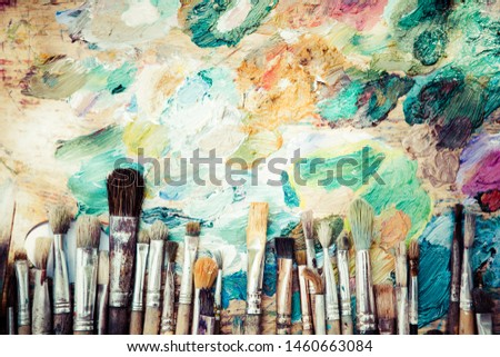 Row artists of Paintbrushes with different sizes lying on dirty artistic palette with free space on top ,background for creative art design (workspace), close, horizontal image #1460663084
