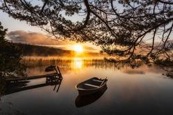 Row boat on calm lake at sunrise