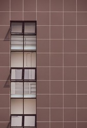 Row glass window panes in vertical line on brown aluminum composite tiles wall of modern office building