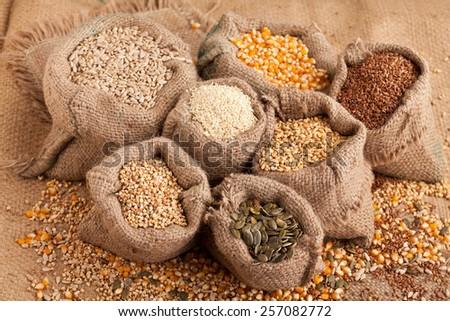 Row healthy grain food (corn, sesame, flax, buckwheat, wheat, pumpkin seeds, sunflower seeds) in jute sack.