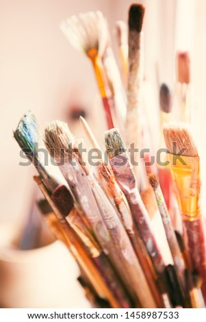 Row in jars with variety of artist paintbrushes, close up, vertical, on light artists studio, nobody