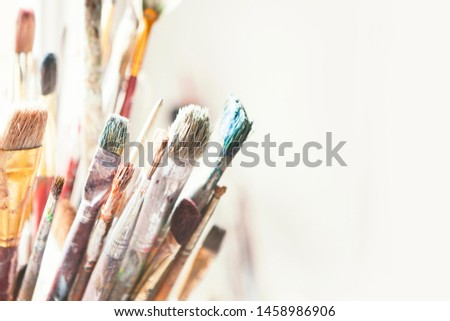 Row in jars with variety of artist paintbrushes with space, horizontal, close up, on white wall, in artists studio, nobody