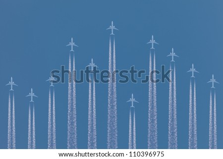 Row of airplanes flying by against a blue sky