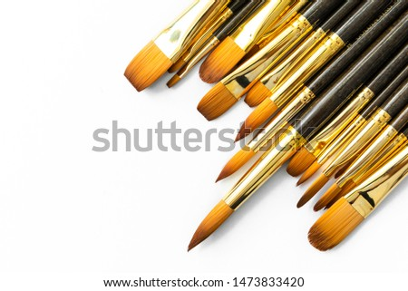 row of artist paint brushes closeup on white background, paintbrushes for wallpaper. #1473833420
