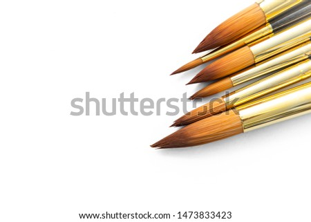 row of artist paint brushes closeup on white background, paintbrushes for wallpaper. #1473833423