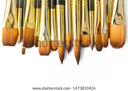 row of artist paint brushes closeup on white background, paintbrushes for wallpaper. #1473833426