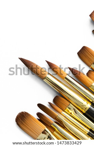 row of artist paint brushes closeup on white background, paintbrushes for wallpaper. #1473833429