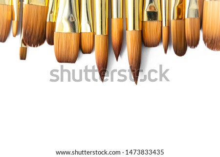 row of artist paint brushes closeup on white background, paintbrushes for wallpaper. #1473833435