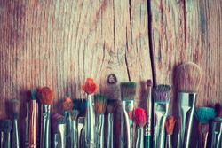 row of artist paintbrushes closeup on old wooden rustic table, retro stylized
