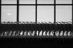 Row of bag pushcart or luggage trolley which is orderly kept at airport terminal, prepare to service for passenger. Photo in shadow - gray lighting shade.