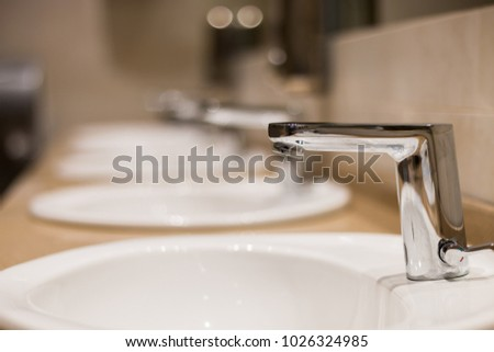 Row of bathroom sinks and faucets with no tap water running. Selective focus on the closest faucet with shallow depth of field. #1026324985