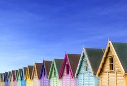row of beach huts with a deep blue sky