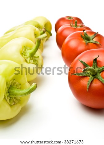 row of bell peppers and tomatoes  against white background