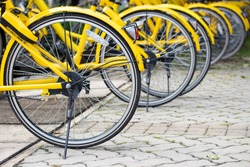 Row of bicycles parked. Yellow bicycles stand on a parking for rent. Pattern vintage bicycles bikes for rent on sidewalk in university. Selective focus.