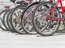 Row of bike wheels parked on concrete pavement. Low angle view of tire tread, gears, and chain. Room for text, copy space.
