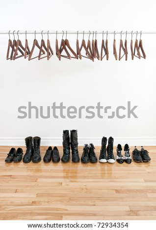 Row of black shoes and boots on a wooden floor, and empty hangers on a rod.