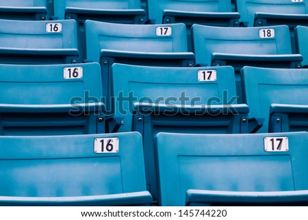 row of blue chairs in a stadium