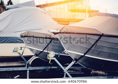 Row of boats in storage for the winter under the awning. Warehouse on the boat pier. Concept preparation for winter. stock photo
