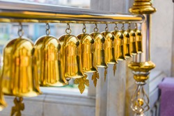 Row of brass bells wind chimes at a Thai Buddhist temple