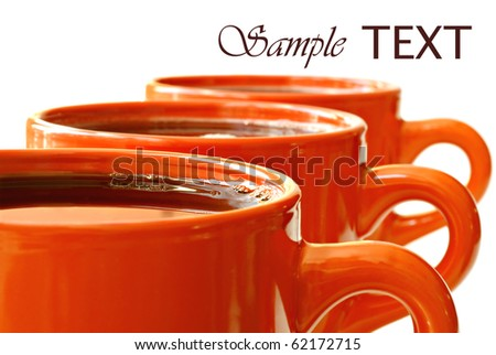Row of bright orange mugs filled with coffee or tea on white background with copy space.  Macro with shallow dof.