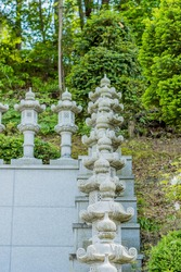 Row of Buddha spirit lanterns on steps up side of wall at local temple.
