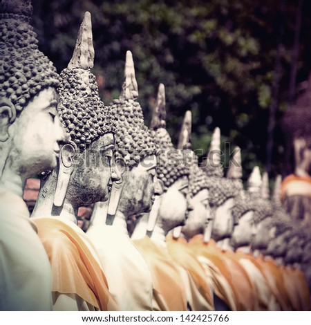 Row of Buddha statue in vintage style